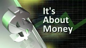 Its about money featured against an electronic graph interafce next t a large silver dollar statue