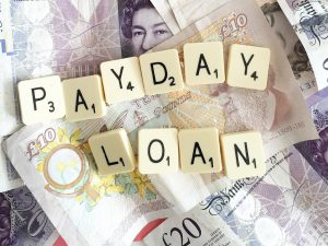 payday loans spelled out on scrabble tokens laying on english banknotes